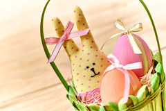 Easter Bunny and painted Eggs in basket on wooden. Easter Bunny Handmade and painted Eggs in decorated green basket with straw on wooden background Stock Photos