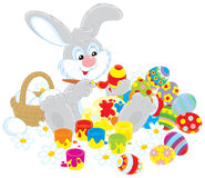 Easter Bunny painter. Grey rabbit painting Easter eggs to the upcoming holiday Royalty Free Stock Photography