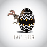 Easter bunny peeking from behind chocolate Easter egg Royalty Free Stock Photography