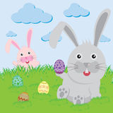 Easter bunny playful with painted eggs Stock Image