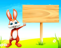 Easter bunny pointing towards wooden sign Royalty Free Stock Images