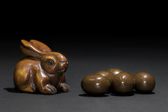 Easter bunny rabbit netsuke with mini Easter eggs. Carved wooden rabbit netsuke looking very much like the Easter bunny next to some mini chocolate truffle Royalty Free Stock Images