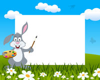 Easter Bunny Rabbit Photo Frame. Easter horizontal photo frame with a cute bunny rabbit painter holding palette and paintbrush, in a meadow with green grass and Stock Photo