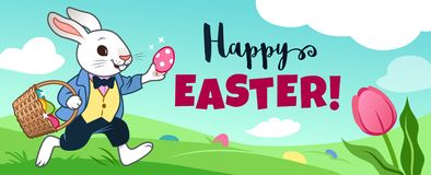 Easter bunny rabbit running in field, carrying basket full of candy eggs, eggs hidden in grass, blue sky with clouds in background royalty free stock photo
