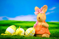 Easter bunny rabbit woman with easter eggs. In green gras Stock Photo