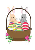 Easter bunny rabbits with Easter basket full of decorated Easter eggs. Stock Photos