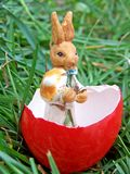 Easter bunny in a red egg. Shell with a mushroom in its hands Stock Photography