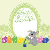 Easter Bunny. Says congratulations. Easter rabbit paints egg Royalty Free Stock Photo