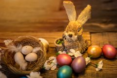 Easter bunny sitting next to a nest filled with colorful easter stock photo