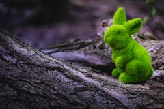 Easter bunny is sitting on a tree trunk royalty free stock images
