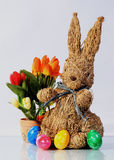 Easter bunny from straw with colored eggs and flower decoration Royalty Free Stock Photography