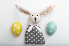 Easter Bunny toy with eggs on ears in a dress Royalty Free Stock Images