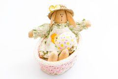 Easter Bunny toy in a pink basket with egg on white background. Stock Image