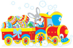 Easter Bunny on a train. Little rabbit on a toy train carrying colorfully decorated Easter eggs Royalty Free Stock Images