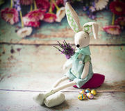 Easter bunny is wating Easter. With flowers and chocolate eggs Royalty Free Stock Images