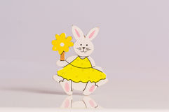 Easter bunny on white background. Easter bunny holding yellow flower on white background Stock Image
