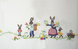 Easter bunny on a white tablecloth. Easter bunny on a white tablecloth embroidered with a cross, Easter theme Royalty Free Stock Images