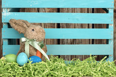 Easter bunny with wood fence. Easter rabbit sits in front of a blue wooden crate with grass and eggs Stock Photos
