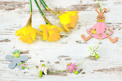 Easter bunny of wood with jonquil. Easter bunny with jonquil on bright wooden background Stock Images