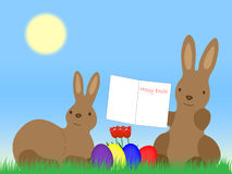 Easter Bunnys with Greeting Card on grassland Stock Image