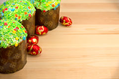 Easter buns and colored Easter eggs. On a wooden board Royalty Free Stock Images