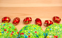 Easter buns and colored Easter eggs. On a wooden board Stock Image