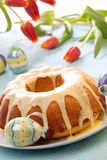 Easter Cake. With lemon icing, decorated with painted eggs and fresh tulips Royalty Free Stock Photography