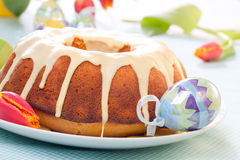 Easter Cake. With lemon icing, decorated with painted eggs and fresh tulips Stock Image