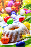 Easter cake. With powdered sugar.Decorated easter eggs and spring tulips stock images