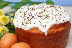 Easter cake and colored eggs yellow flower blossoms on background. Holiday food and easter concept. Selective focus. Copyspase. Easter cake and colored eggs royalty free stock images