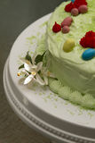 Easter Cake. Colored in green to resemble grass, decorated with red flower and easter eggs, with a cream cheese frosting Royalty Free Stock Photography