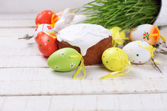 Easter cake, colorful easter eggs, grass on white wooden backgro Stock Images
