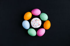 The Easter cake and colourful eggs on a black table Stock Image