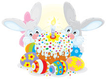 Easter cake and eggs. Grey bunnies with a colorfully decorated Easter cake and painted eggs Stock Images