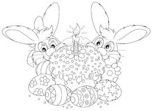 Easter cake and eggs. Friendly smiling bunnies, decorated Easter cake and painted eggs, black and white outline illustration for a coloring book Royalty Free Stock Images