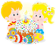 Easter cake and eggs. Girl and boy with a colorfully decorated Easter cake and painted eggs Stock Photos