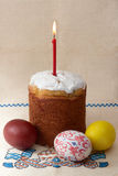 Easter cake with eggs and candle. Traditional russian Easter cake - kulich - with easter eggs and candle  on unbleached linen with embroidery Stock Images
