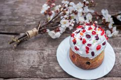 Easter cake garnished with dried cherries and cranberries stands on a wooden table, lies near a bouquet of blooming. Easter sweet bread Orthodox kulich, paska stock photography