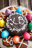 Easter cake, hot cross buns and colored eggs Stock Photo