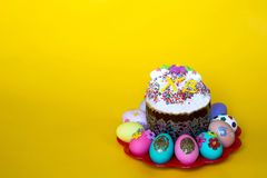 Easter cake with icing and colored Easter eggs on yellow background royalty free stock photo