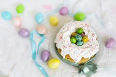 Easter cake with icing and colorful Easter eggs with light blue ribbons Royalty Free Stock Photos