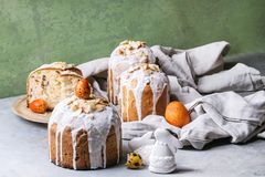 Easter cake Kulich. Set of traditional Russian and Ukrainian Easter cake Kulich Paska bread glazed with almond, whole and sliced, served on ceramic plate with Royalty Free Stock Photo
