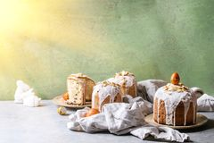 Easter cake Kulich. Set of traditional Russian and Ukrainian Easter cake Kulich Paska bread glazed with almond, whole and sliced, served on ceramic plate with Royalty Free Stock Photos