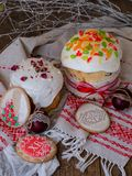 Easter cake kulich. Traditional Easter sweet bread decorated meringue, pink dry roses, red eggs and cookies in form of Easter eggs stock image