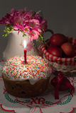 Easter cake with a lit candle, flowers and painted eggs Stock Photography