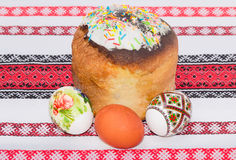 Easter cake and several different Easter eggs on a tablecloth Royalty Free Stock Photography