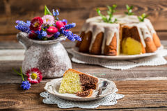 Easter cake and spring flowers. On old wooden table Stock Photos