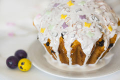 Easter cake with sugar glaze with yellow and violet sugar butterflies and tree colorful Easter eggs Royalty Free Stock Image