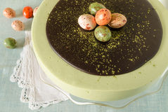 Easter cake with tea matcha decorated chocolate ganache and sweet-stuff eggs. Near cup of coffee. From series elegant desserts Royalty Free Stock Photo