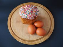 An easter cake with three eggs on the wooden board stock photography